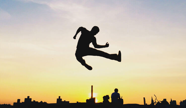 Silhouette of kid jumping against sunset